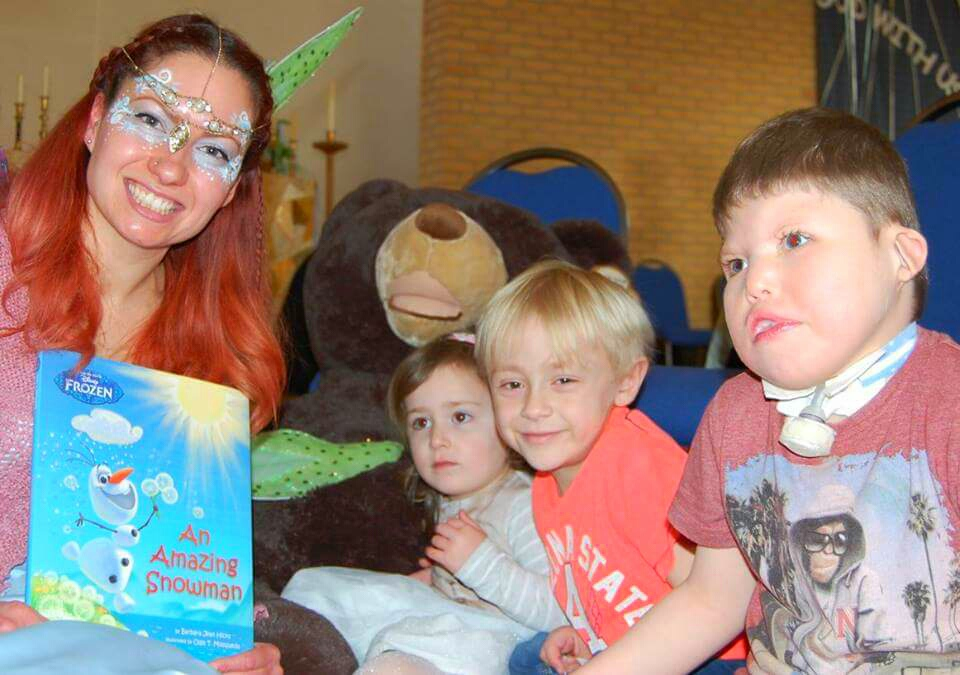 Viola Fairy reads to children from Julia\'s House